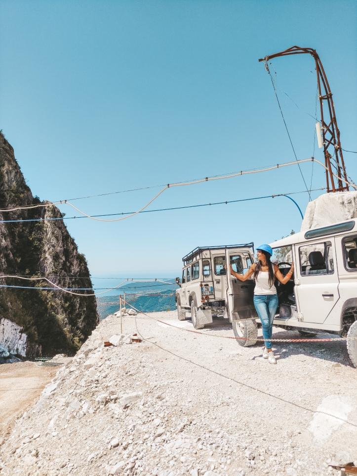 Ragazza scesa da una jeep 4x4 che osserva le cave di marmo di Carrara
